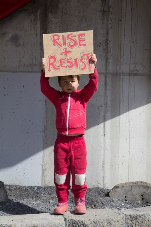 One of many children donning red at the Women's March on Wednesday, Leo holds a sign outside of City Hall.
