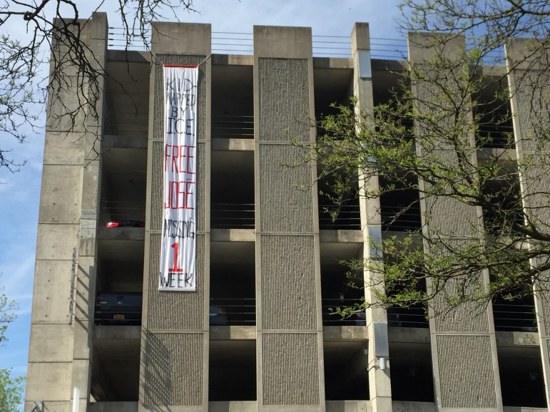A banner on the Seneca Street parking garage on Tuesday, protesting the arrest of José Guzman-Lopez
