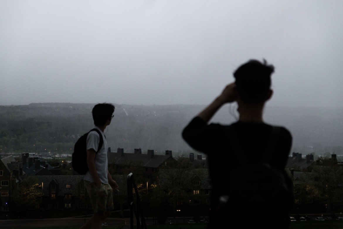 Students watch from the top of Libe Slope as a storm approaches Ithaca. There is a tornado watch for Tompkins County until 10 p.m.