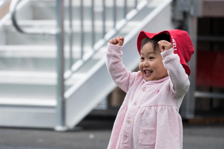A young child celebrates senior convocation at Cornell on Saturday, where Joe Biden spoke to thousands of graduating seniors and their families.