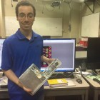Kyle Doyle, a doctoral student who helps lead the Cornell CubeSat group, holds the finished product: a spacecraft that NASA will send into space.