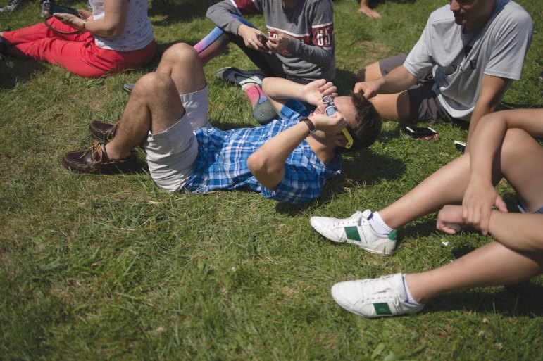 A Cornell student marvels at the solar eclipse on Monday afternoon as he relaxes on the grass.