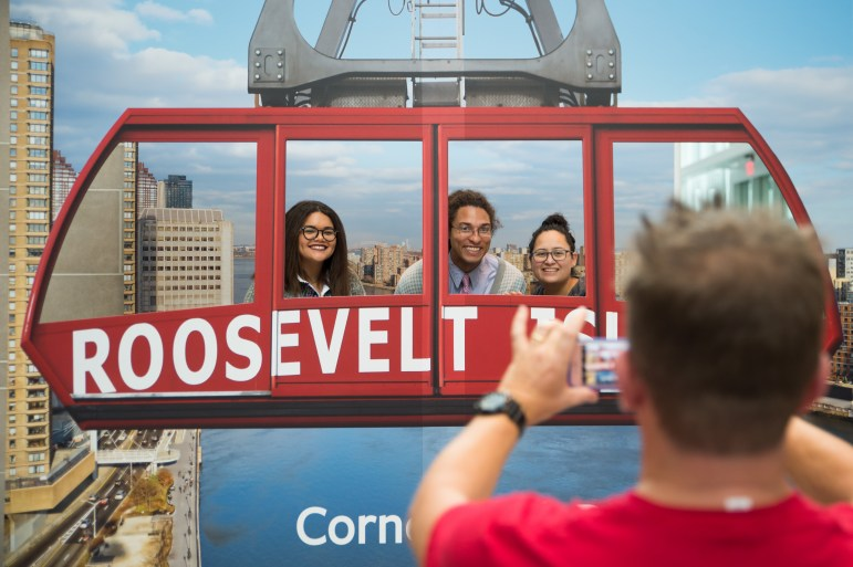 Amanda Williams '17, Reid Palmer, and Erin Rodriguez, workers in the College of Business Admissions Office, pose for pictures to commemorate the opening and dedication of Cornell Tech in New York City, September 13th, 2017. (Cameron Pollack / Sun Photography Editor)