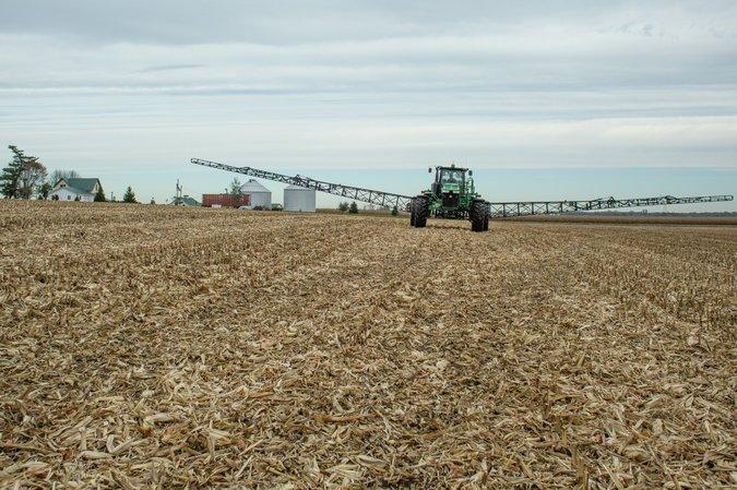 A tractor sprays nitrogen-based fertilizers on a corn field in Leesburg, Virginia.