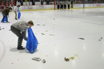 Rink attendants collect fish thrown by the Cornell students in a tradition that spawns over decades.