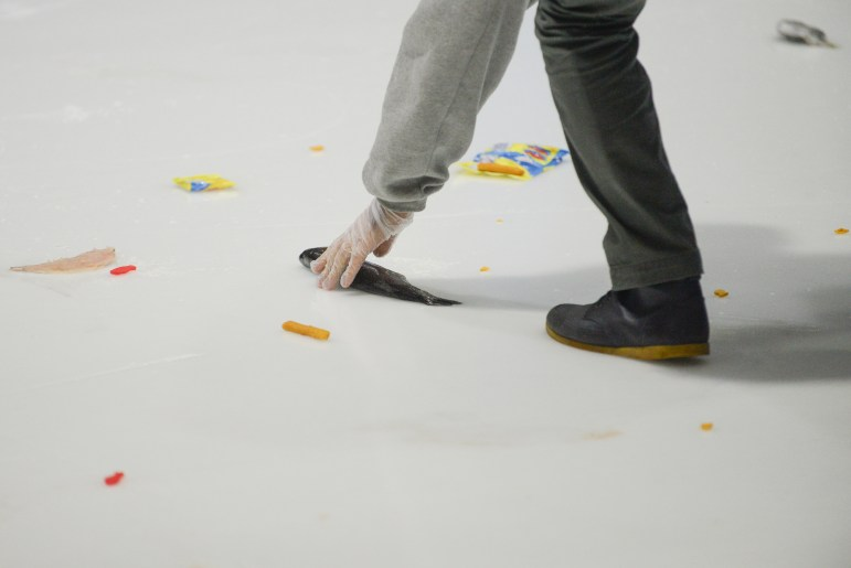 A rink attendant collect fish thrown by the Cornell students in a tradition that spans over decades. (Cameron Pollack/ Sun Photography Editor)