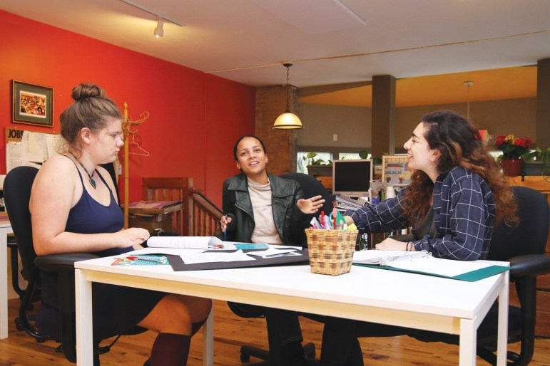 Youth fellows Ahja Haedicke, left, and Lyla Zusman, right, discuss their People's Budget program with Emma Dennis, center, a former youth facilitator who now helps oversee the fellows.
