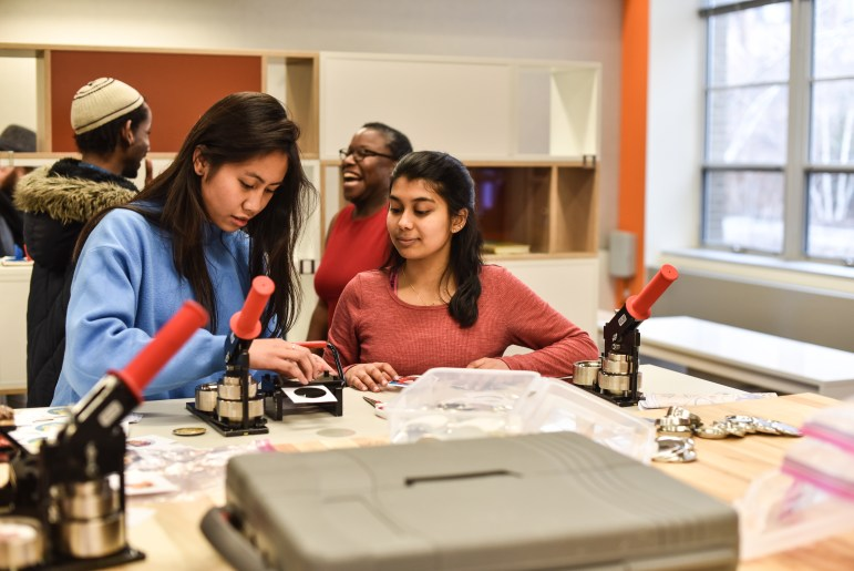 Students make buttons at the opening of MannUfactory on Thursday.
