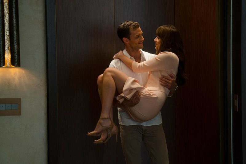 Christian Grey (Jamie Dornan) carries Anastasia Steele (Dakota Johnson) in Fifty Shades Freed.