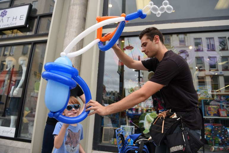 Balloon twister and magician Brandon Axelrod fashions a scuba diving tank out of balloons for a child at the C.U. Downtown event on Saturday.