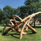 The LOG KNOT installation is composed of irregularly-shaped logs connected in a twisting design.
