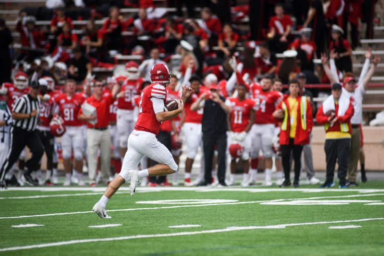 The crowd cheers on junior quarterback Mike Catanese as he makes his way to the endzone for a touchdown, tying the game 14-14. Catanese's rushes played an important role in the Red's comeback victory over Harvard. (Boris Tsang / Sun Assistant Photography Editor)