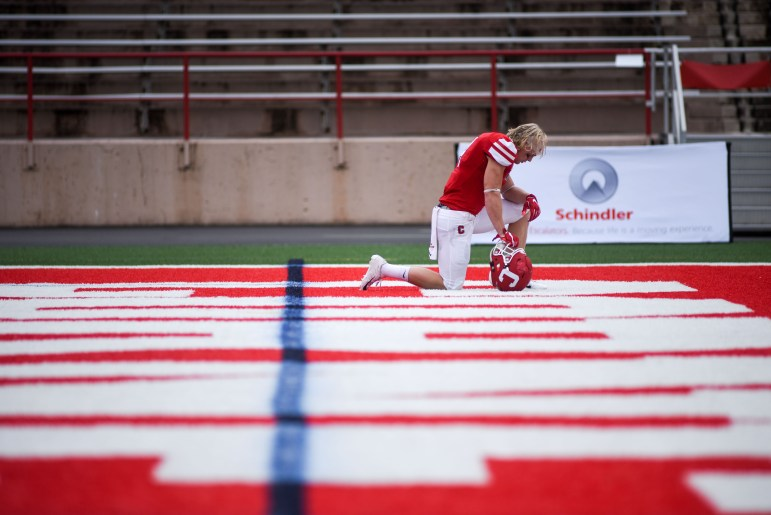 Senior running back J.D. PicKell prays before the game against Harvard on Saturday. (Boris Tsang / Sun Assistant Photography Editor)