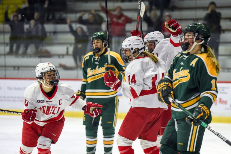 The women's hockey team celebrates after junior defenseman Jaime Bourbonnais scores Cornell's second goal against Clarkson on Saturday. The goal put the Red up 2-1 en route a 3-1 victory over the two-time defending national champions. (Boris Tsang / Sun Assistant Photography Editor)