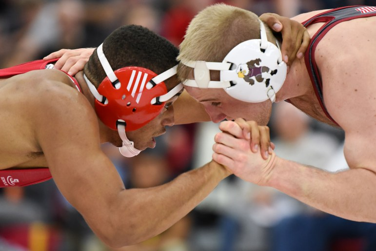 Junior Chas Tucker grapples with his opponent at the wrestling match against Lock Haven on Saturday. (Boris Tsang / Sun Assistant Photography Editor)