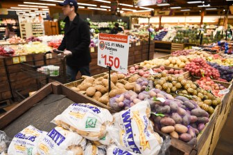 A customer shops the reduced price potatoes in the produce section.
