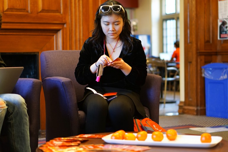Caitlin Lau '22 scratches her fortune card at the Lunar New Year Celebration at the Tatkon Center on Monday. (Michelle Yang / Sun Staff Photographer)