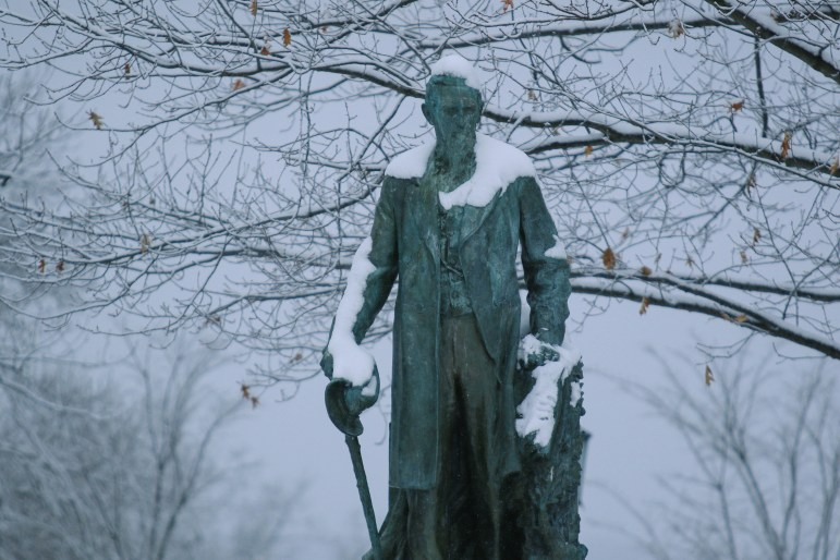 A statue of Ezra Cornell is in the Arts Quad gets dusted with snow during Cornell's last snow day, in March 2018.