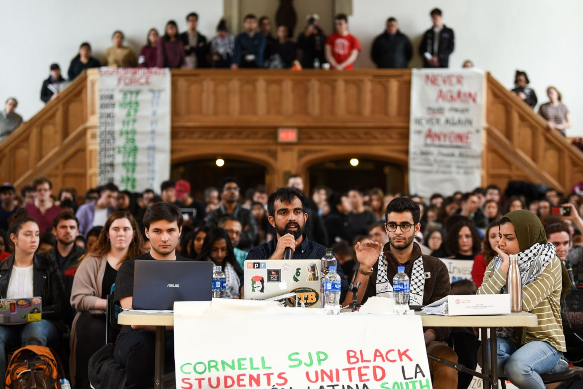 Omar Din '19, center, a representative on Student Assembly and member of the Convocation Committee, speaks in favor of the divestment resolution at a meeting on Thursday.