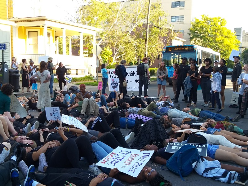 Protestors staged a die in on North Tioga Street, blocking the TCAT Route 10, over the April arrests of Rose Degroat and Cadji Ferguson.