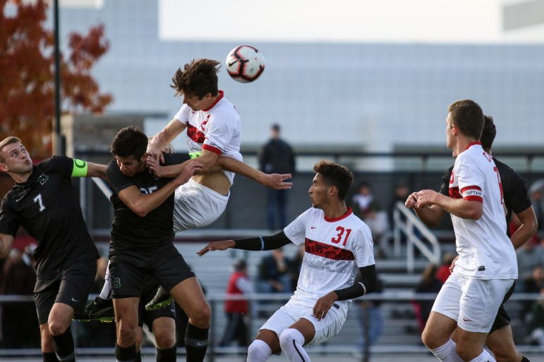 Senior defender Ryan Bayne heads the ball at the soccer game against Brown on Saturday. The match ended in a 1-1 draw. (Michael Wenye Li/Sun Senior Photographer)