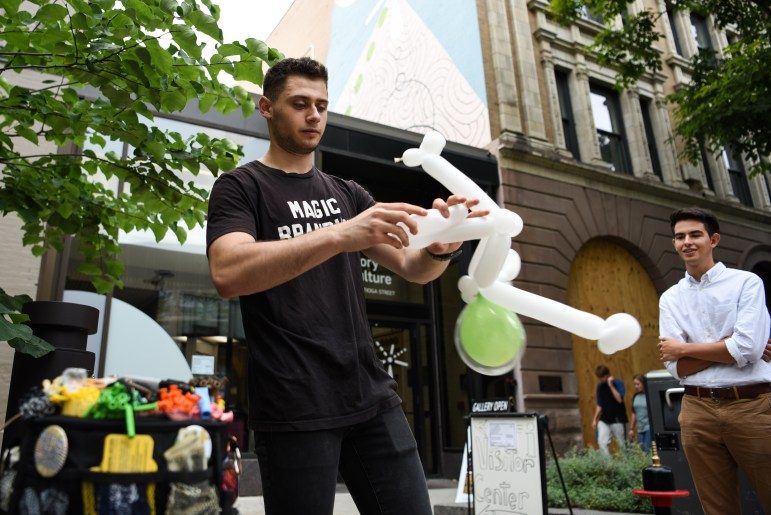 Brandon Axelrod fashions an alien astronaut out of balloons during C.U. Downtown at the Ithaca Commons on September 7th, 2019.