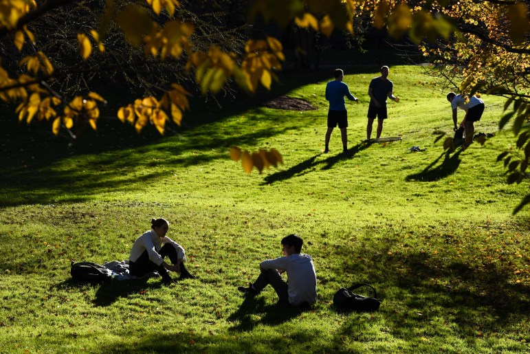 Students relax in the clearing by Sage Hall after class on Monday. (Boris Tsang/Sun Photography Editor)