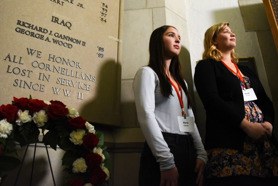 Maria Gannon, left, daughter of Major Richard Gannon '95, and Maria Wood, daughter of Captain George Wood '93, stand by the war memorial in the rotunda of Anabel Taylor Hall during the war memorial dedication on Nov. 9, 2019.