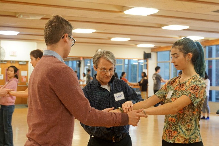 Two students hold hands in Intro to Swing Dance.