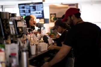 Baristas work in Libe Cafe serving customers.