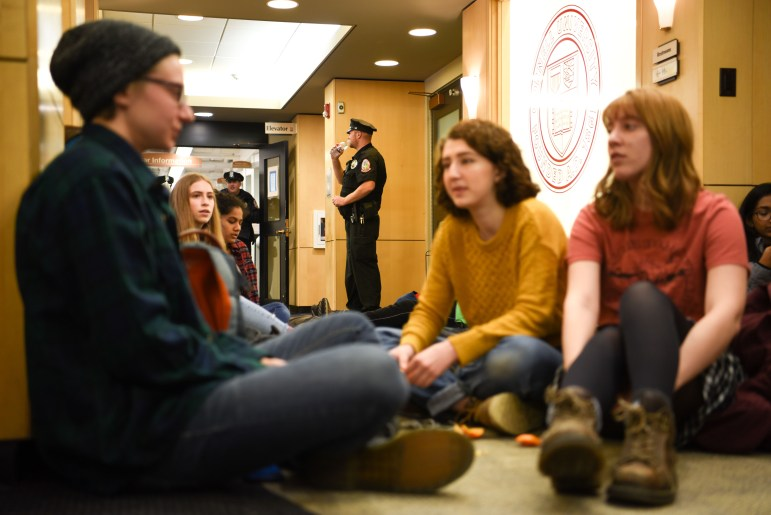 Students sit on the floor of the lobby of Day Hall as CUPD officers in the background restrict access to the stairwell and hallway during the climate strike on Friday. (Boris Tsang/Sun Photography Editor)