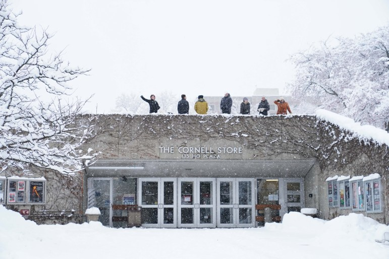 Students throw snow balls from the top of the Cornell Store on Monday after the University cancelled all classes and closed the Ithaca campus. (Ben Parker/Sun Assistant Photography Editor)