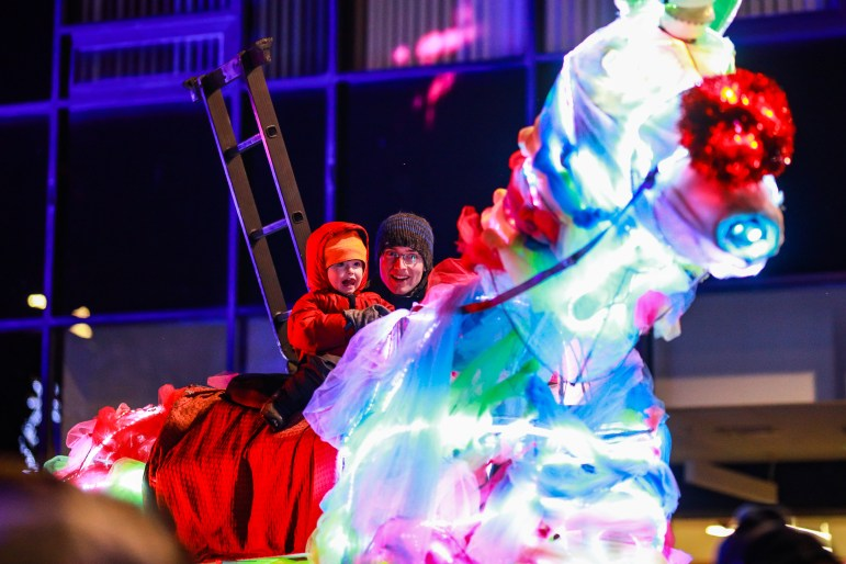 A child climbs atop a light-up unicorn at the Ithaca Commons on Friday. The unicorn was part of the inaugural Winter Light Festival, which kicked off on Thursday. (Michael Wenye Li/Sun Senior Photographer)