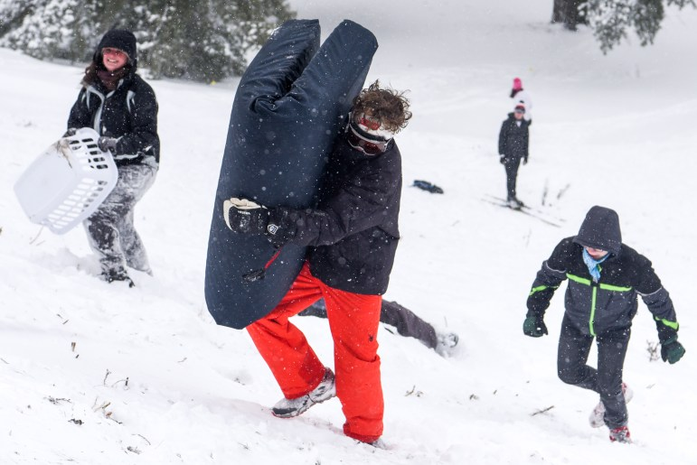 A student climbs up Libe Slope with a mattress while another carries a laundry basket during the snow day on Friday. (Boris Tsang/Sun Photography Editor)