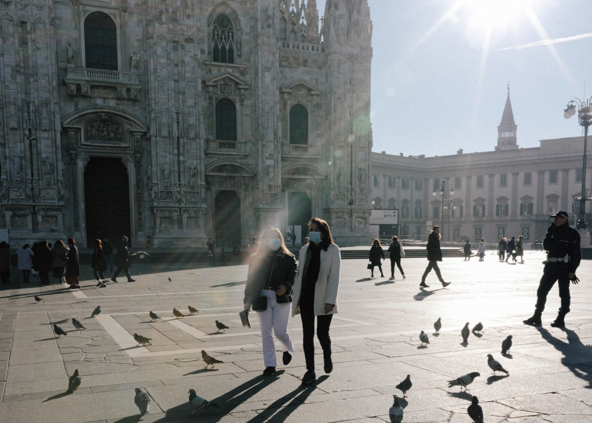 Two masked tourists walk by Milan's Duomo Cathedral. As Coronavirus has spread heavily to Italy and South Korea, Cornell suspends its study abroad programs.
