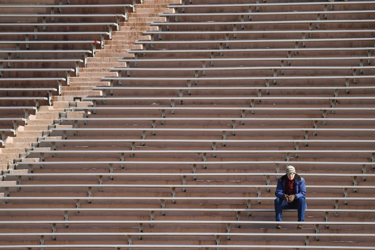 A fan watches the women's lacrosse game against Columbia on Saturday from the bleachers of Schoellkopf Field. (Ben Parker/Sun Assistant Photography Editor)
