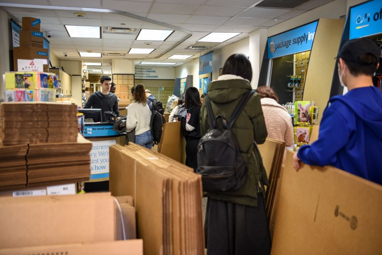 Students take to the UPS store in Collegetown to stock up on boxes to move out of Ithaca, following President Martha E. Pollack's Friday afternoon announcement urged immediate return home.