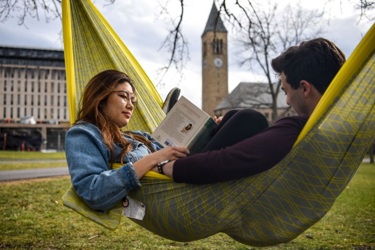Kelly Song '20, left, and Nick Diaco '21 read in a hammock on the Arts Quad on Friday, as McGraw Tower poked up behind them. After scattered thunderstorms in the morning, temperatures peaked in the 60s in the afternoon, the nice weather inviting students to lounge outside. (Boris Tsang/Sun Photography Editor)