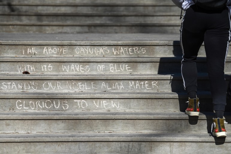 """Lines of the alma mater, """"Far Above Cayuga's Waters,"""" cover the steps by Balch Hall today in chalk. Freshman ran around North Campus preparing to leave Cornell for the semester. (Boris Tsang/Sun Photography Editor)"""