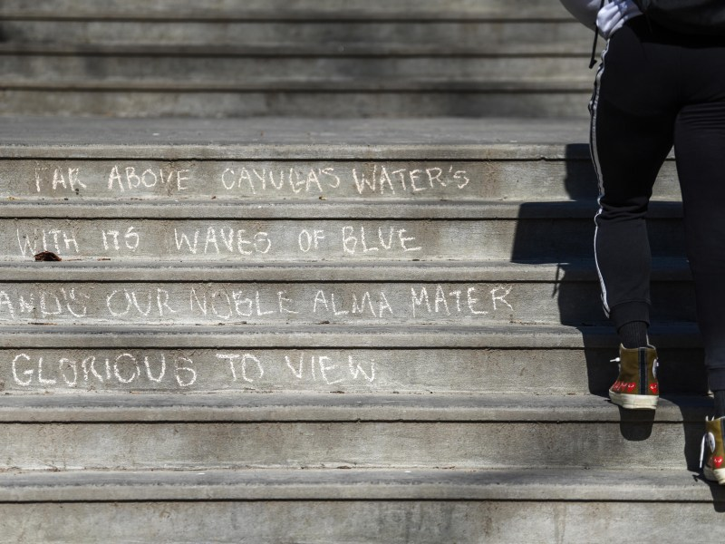 "Lines of the alma mater, ""Far Above Cayuga's Waters,"" cover the steps by Balch Hall on Sunday in chalk. Freshman ran around North Campus preparing to leave Cornell for the semester. (Boris Tsang/Sun Photography Editor)"