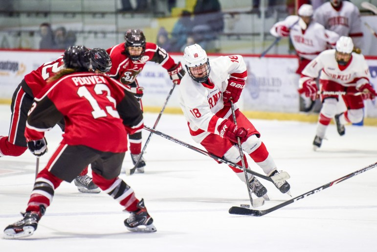 Senior forward Paige Lewis navigates the puck between St. Lawrence players on Saturday. After a tie for most of the game, the women's hockey team took home the 3-2 win. (Boris Tsang/Sun Photography Editor)