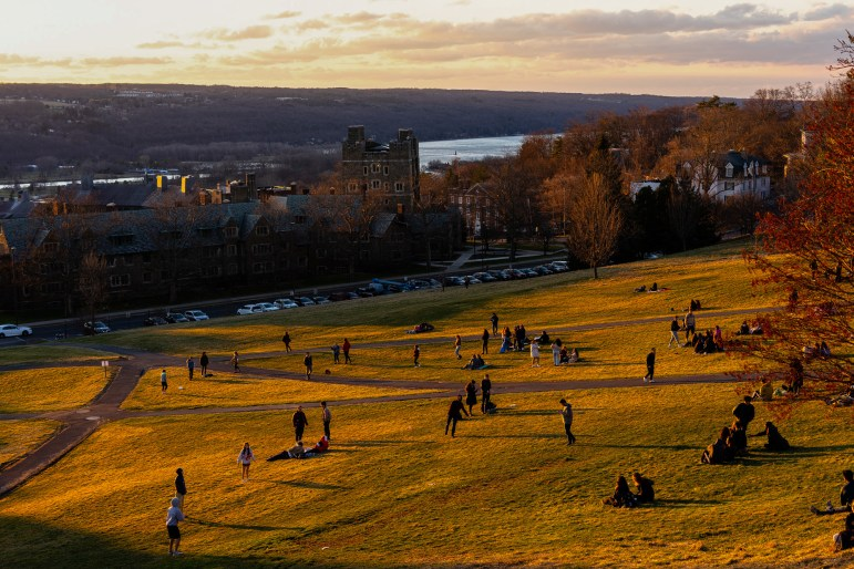 Students hung out on Libe Slope on Friday, soaking in the warm weather after receiving President Pollack's announcement about the latest status of COVID-19 and in-person classes on campus. (Harry Dang/Sun Staff Photographer)