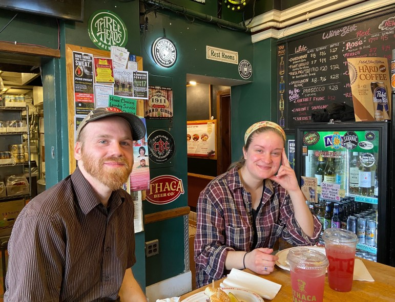 Collegetown Bagels employees Robbie Finch and Paige Twining sit in the College Ave. restaurant on Thursday. Finch said he isn't worried about the impact of Cornell's shift to online classes, but expects CTB to have summer-sized crowds during April and May.