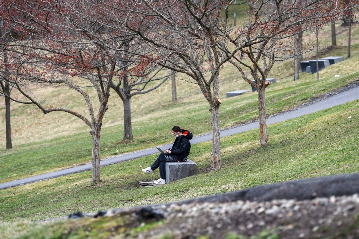 A student sits alone on Libe Slope, practicing social distancing in light of COVID-19.