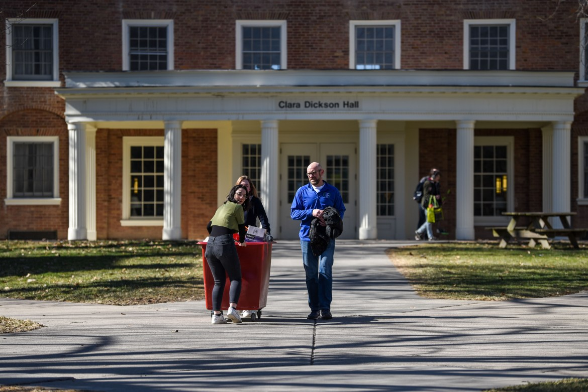 A student rolls her belongings out of Dickson Hall on March 15, 2020.
