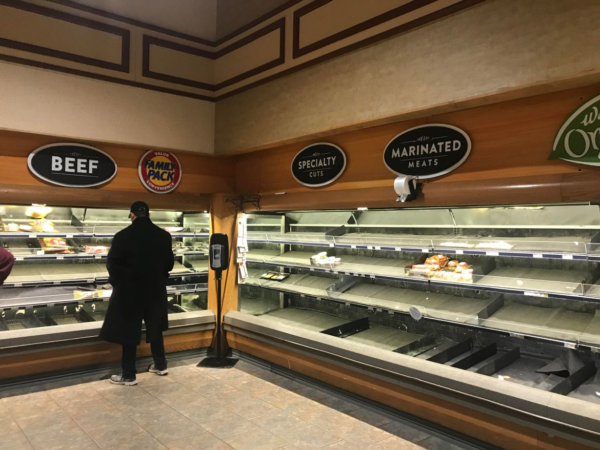 Customers browse a nearly-empty Wegmans meat section on Thursday evening.