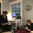 Prof. Suzanne Charles works in her bedroom while her son, who often makes cameos in her video lectures, reads a book.