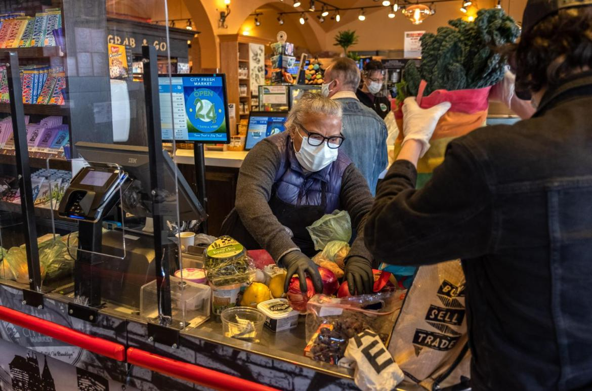 A cashier checks out a customer at a grocery store in Brooklyn, New York