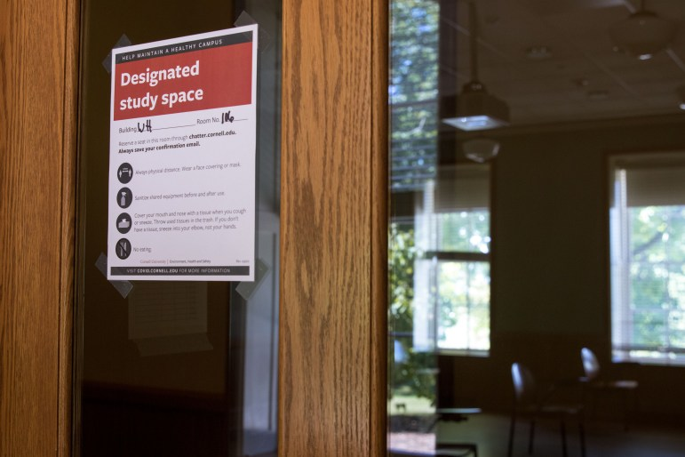 Signs adorn doors to study spaces around campus, advising social distancing procedures and occupancy limits.