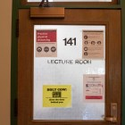 A Plant Science classroom door has Covid-19 precautions plastered to it.